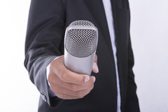Man in business suit holding microphone - interview concept Royalty Free Stock Photos
