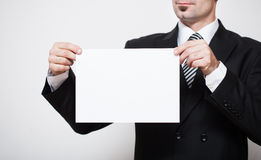 Man in business suit holding white paper in hands. Free space for your text Royalty Free Stock Images