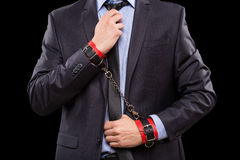 Man in a business suit with leather bound. A man in a business suit with leather bound with handcuffs. sex Toys royalty free stock image
