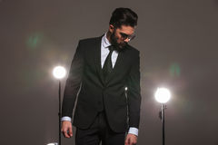 Man in business suit looking down in studio with spotlights on Royalty Free Stock Image