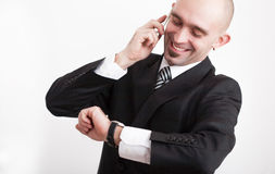 Man in business suit looking on watch while talking on mobile phone Royalty Free Stock Images