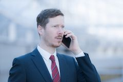 Man in business suit is making a phone call and he`s surprised. A handsome man is on the phone, he`s surprised. He`s wearing a dark blue suit and a red neck tie Royalty Free Stock Images
