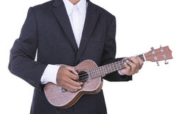 Man in business suit playing ukulele Stock Images