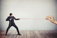 Man in business suit is pulling the rope. A man in dark business suit is vigorously pulling the rope from the one end while a female's hand is holding another Royalty Free Stock Images