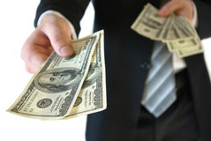 Man in a business suit put money in your pocket Stock Image