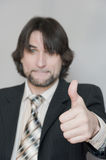 man in a business suit shows a sign of Stock Image