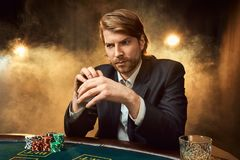 A man in a business suit sitting at the game table. Male player. Passion, cards, chips, alcohol, dice, gambling, casino. It is as male entertainment royalty free stock photography