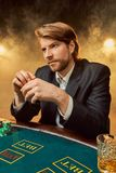 A man in a business suit sitting at the game table. Male player. Passion, cards, chips, alcohol, dice, gambling, casino Royalty Free Stock Images