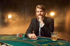 A man in a business suit sitting at the game table. Male player. Passion, cards, chips, alcohol, dice, gambling, casino Royalty Free Stock Image