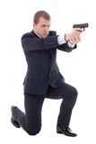 Man in business suit sitting on knee and shooting with gun isola Stock Photos