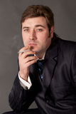 Man in a business suit smoking a cigarette Stock Images