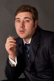 Man in a business suit smoking a cigarette Royalty Free Stock Images