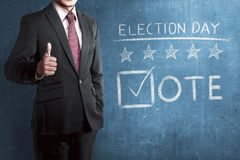 Man with business suit standing beside 'Election Day' Stock Photo