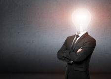 Man in a business suit stands, behind him empty concrete wall. Instead of head businessman lighting bulb. Bussines, idea Royalty Free Stock Images