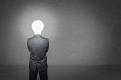 Man in a business suit stands with his back, before him empty concrete wall. Instead of head businessman lighting bulb Royalty Free Stock Photos