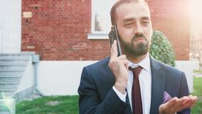 Man in business suit talking on the phone, outdoor in the city