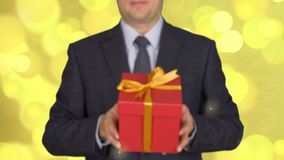 A man in a business suit with a tie is holding a red gift box. A man gives a gift. A businessman with a gift in his stock video footage