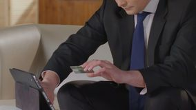 Man in business suit typing credit card number on tablet screen, paying bills. Stock footage stock footage