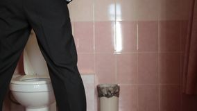 Man in a business suit using a toilet.  stock footage