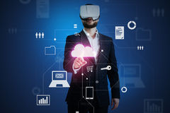 Man in business suit and VR-headset touching a cloud icon on vi Royalty Free Stock Photos