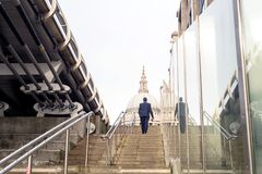 St Pauls Cathedral Man Walking Steps. Man in business suit walking up steps towards St Pauls Cathedral in London England Royalty Free Stock Photo