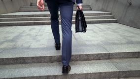Man in business suit walking upstairs holding briefcase beginning of working day royalty free stock images
