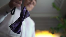 A man in a business suit, a white shirt, holds a violet or blue bow tie in his hand. A businessman puts on a bowtiek for stock video footage