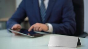 Man in business suit working on tablet pc, blank nameplate template for text. Stock footage stock video
