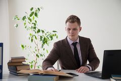 A man in a business suit works at the computer with books in the Office. 1 Royalty Free Stock Photos