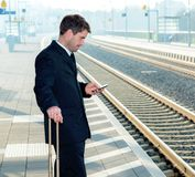 Man on business trip using his smartphone Stock Photography