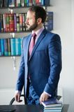 Man businessman with beard in blue formal suit at workplace. Man businessman with beard in blue formal suit stand at workplace desk in office. Business Stock Photo