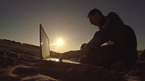 Man businessman freelancer working behind laptop sitting on beach freelancing silhouette in the sun Royalty Free Stock Image