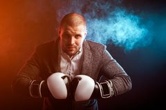 Man businessman in gray suit and boxing gloves. Young intelligent man businessman in white shirt, gray suit, black and white boxing gloves posing in against a Stock Image