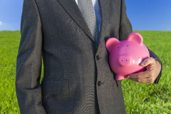 Man Businessman Holding Piggy Bank in Field Royalty Free Stock Photos