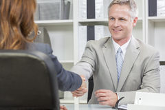 Man or Businessman Office Handshake Female Colleague. Man or businessman shaking hands handshake in office meeting with female colleague stock photography