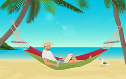 Man businessman sitting in hammock on the sea beach and working with his laptop computer. Best place for work. Stock Photo