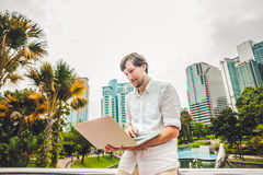 Man businessman or student in casual dress using laptop in a tropical park on the background of skyscrapers. Dressing in a white s Royalty Free Stock Photo
