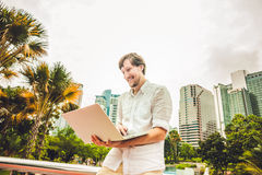 Man businessman or student in casual dress using laptop in a tropical park on the background of skyscrapers. Dressing in a white s Royalty Free Stock Image