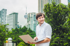 Man businessman or student in casual dress using laptop in a tropical park on the background of skyscrapers. Dressing in a white s Royalty Free Stock Photos