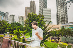 Man businessman or student in casual dress using laptop in a tropical park on the background of skyscrapers. Dressing in a white s Stock Photography