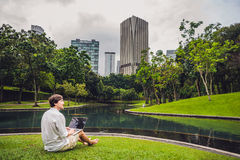 Man businessman or student in casual dress using laptop in a tropical park on the background of skyscrapers. Dressing in a white s Royalty Free Stock Images