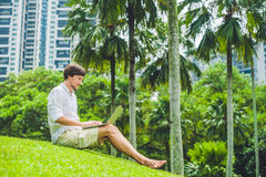 Man businessman or student in casual dress using laptop in a tropical park on the background of skyscrapers. Dressing in a white s Stock Photos