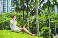 Man businessman or student in casual dress using laptop in a tropical park on the background of skyscrapers. Dressing in a white s Stock Photo