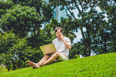 Man businessman or student in casual dress using laptop in a tropical park on the background of skyscrapers. Dressing in a white s Royalty Free Stock Photography