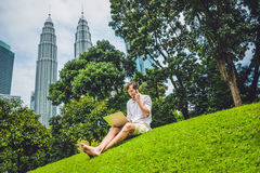 Man businessman or student in casual dress using laptop in a tropical park on the background of skyscrapers. Dressing in a white s Stock Images