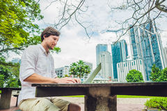 Man businessman or student in casual dress using laptop in a tropical park on the background of skyscrapers. Dressing in a white s Stock Image