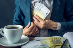 Man Businessman in suit puts money in his pocket. A bribe in the form of Euro bills. Concept of corruption and bribery. Man Businessman in suit puts money in his Stock Photography