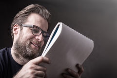 Man businessman in t-shirt and glasses reading documents Royalty Free Stock Photography