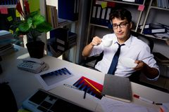 The man businessman working late hours in the office. Man businessman working late hours in the office Stock Images