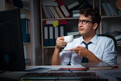 The man businessman working late hours in the office. Man businessman working late hours in the office Stock Photography